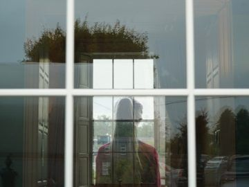 A woman is seen from behind, through a pane d glass window. The image is ethereal and washed out.